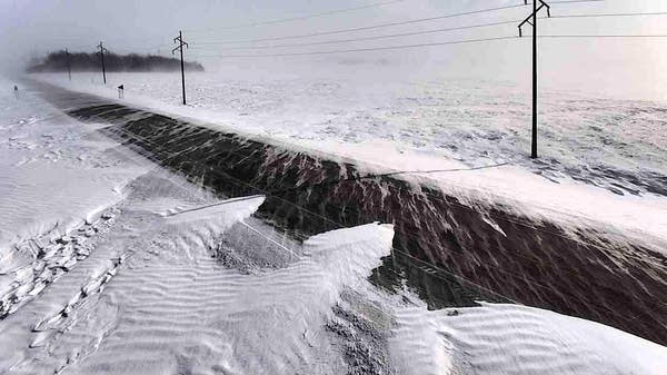 Drifting snow encroaches on the driving lanes of State Highway 7