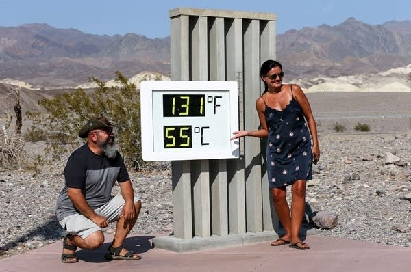 Visitors in front of an unofficial thermometer at Death Valley.