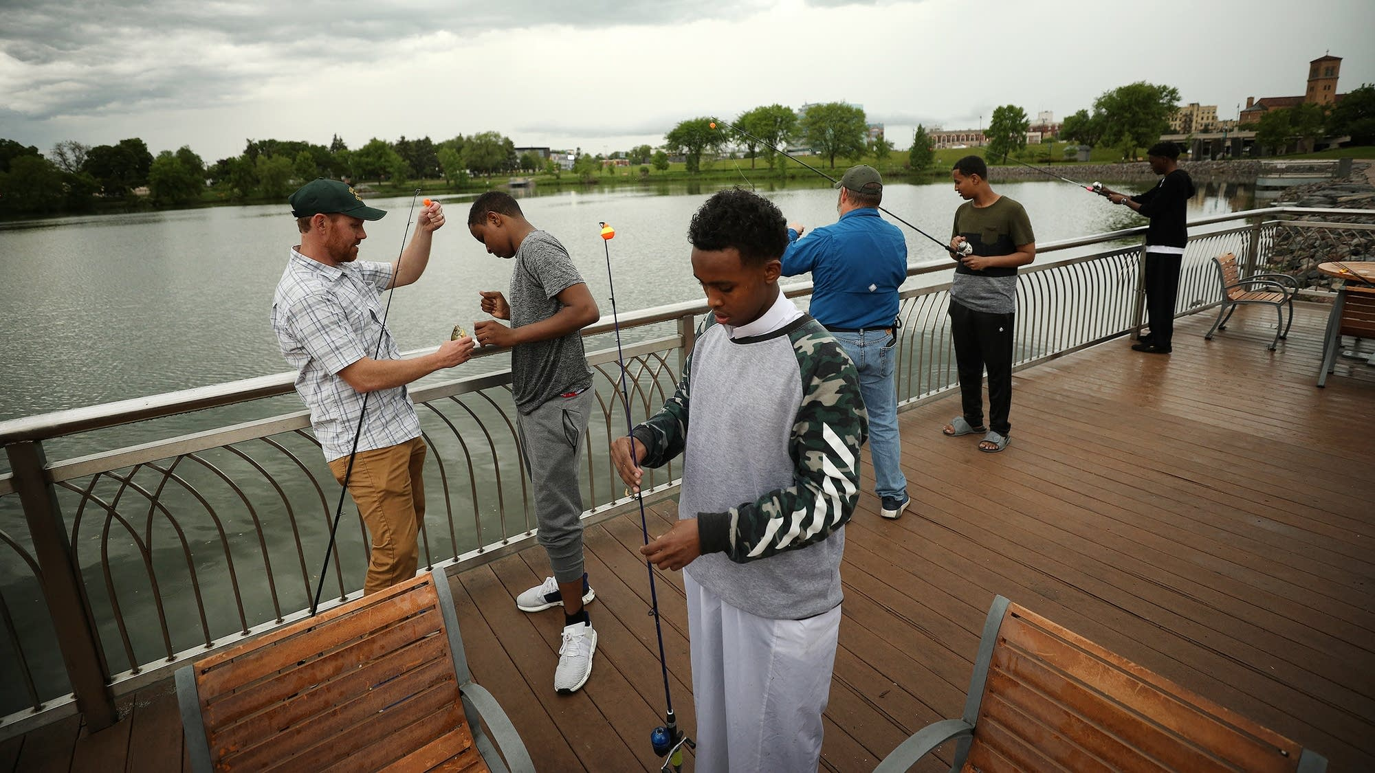 Members of the Somali community learn to bait a hook and cast a line.