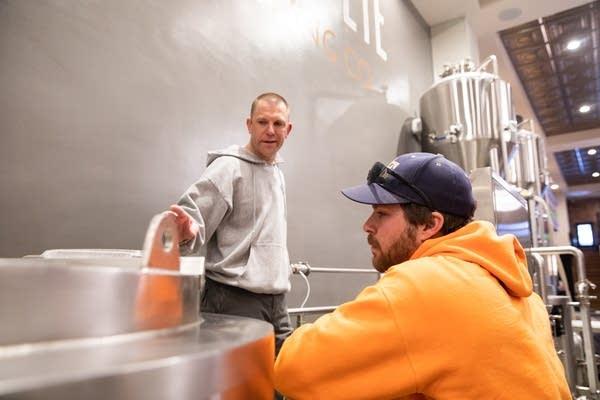 Two men talk inside of brewery.