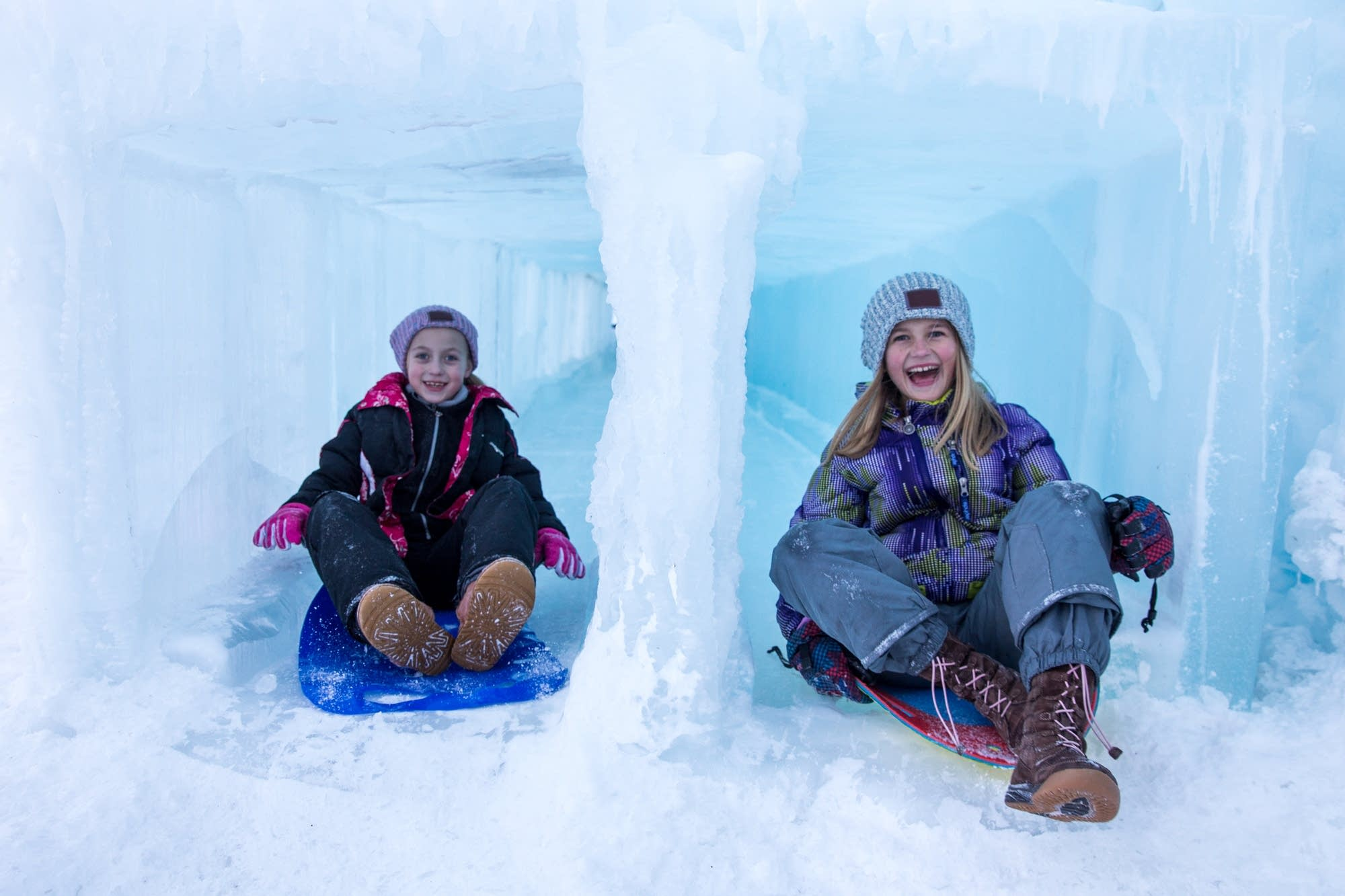 Young girls race down the ice slide.
