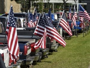 Dozens of American flags fly from a row of student vehicles.