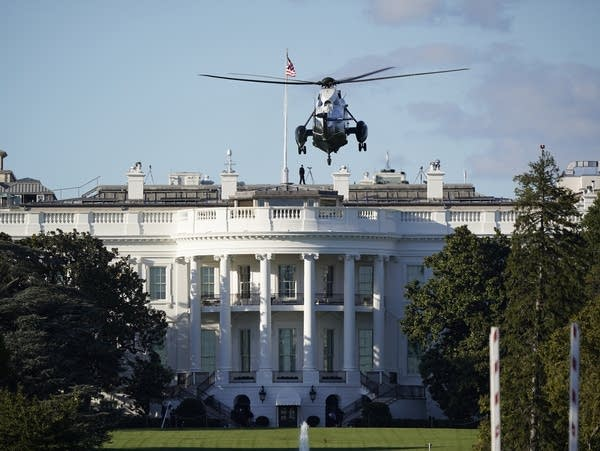 A helicopter hovers above the White House.