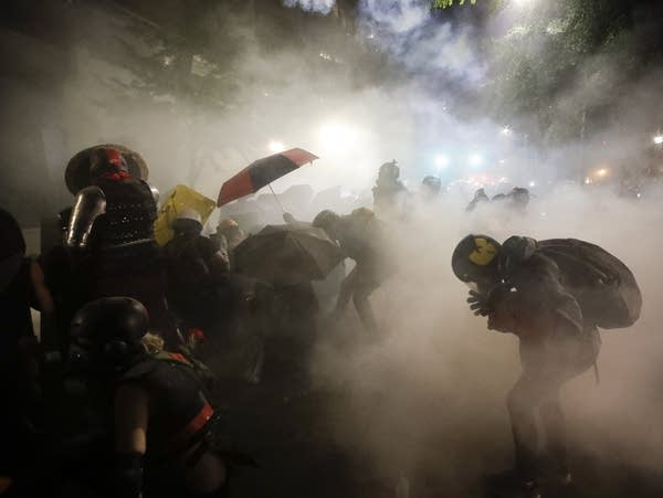 Federal officers launch tear gas at a group of demonstrators
