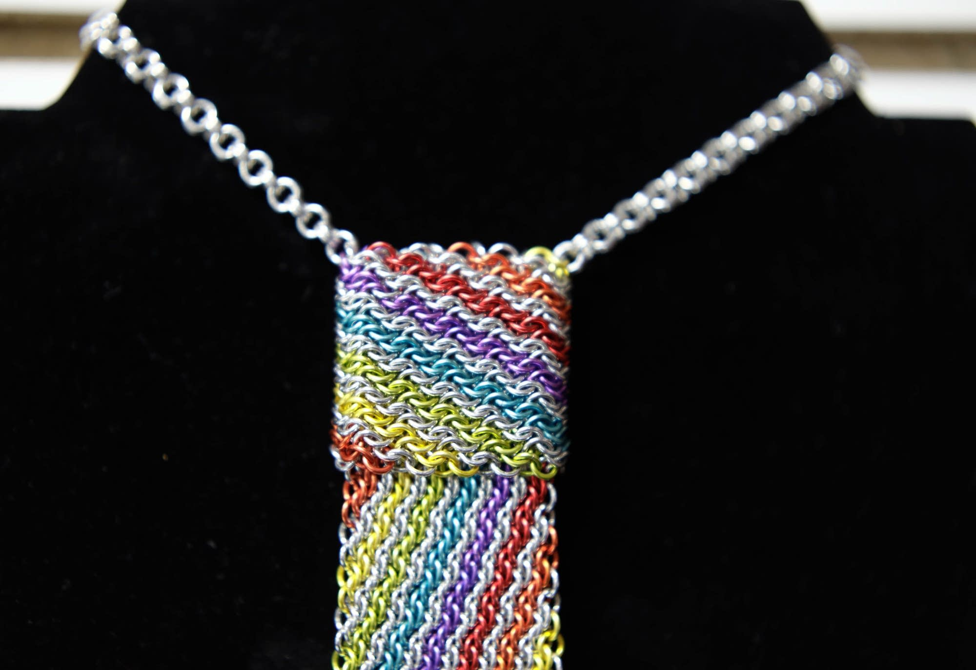 A colorful tie made with the chainmaille rings is displayed.
