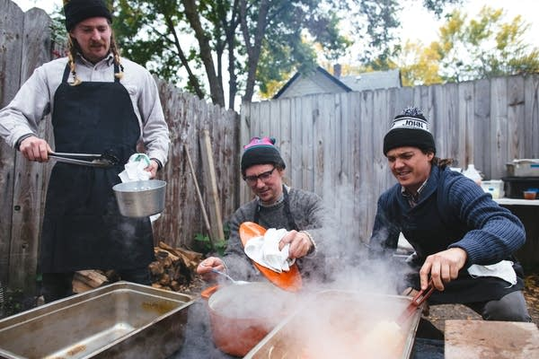 Three men cook outside