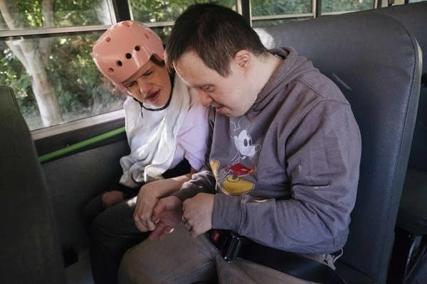 Sarah Gonella and David G. hold hands on the bus to work.