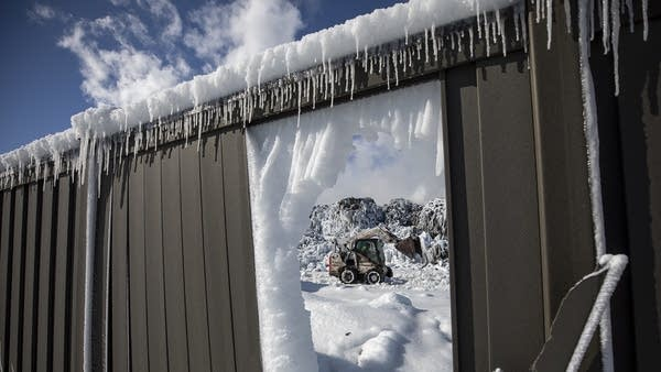 A pile of ice-covered cars seen through a whole in a metal wall.