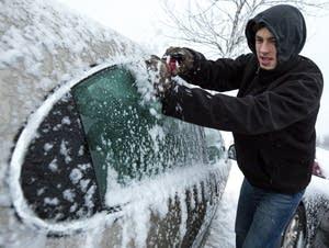 SCSU student Dalton Foley scrapes ice off his car.