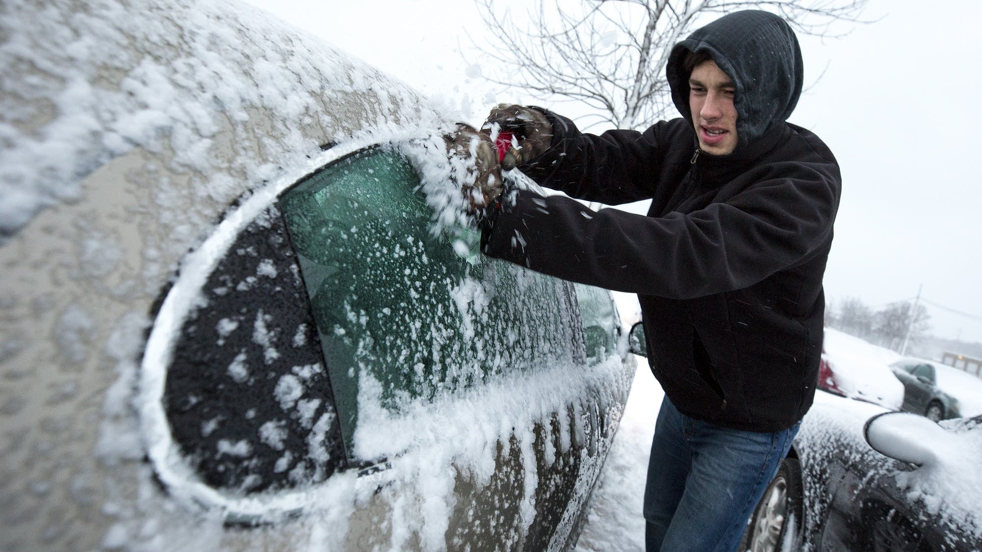 SCSU student Dalton Foley scrapes ice off his car.