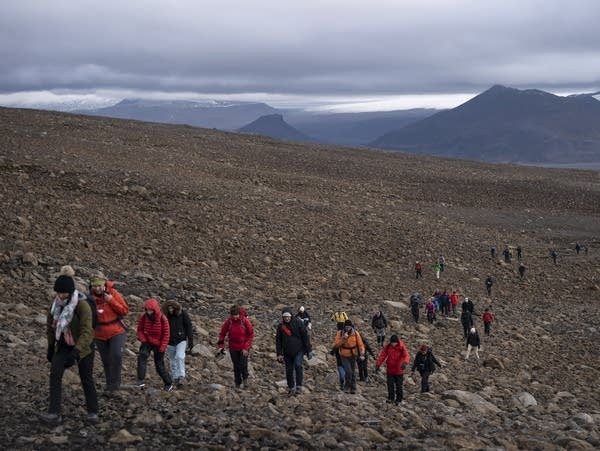 People climb to the top of what once was the Okjokull Glacier