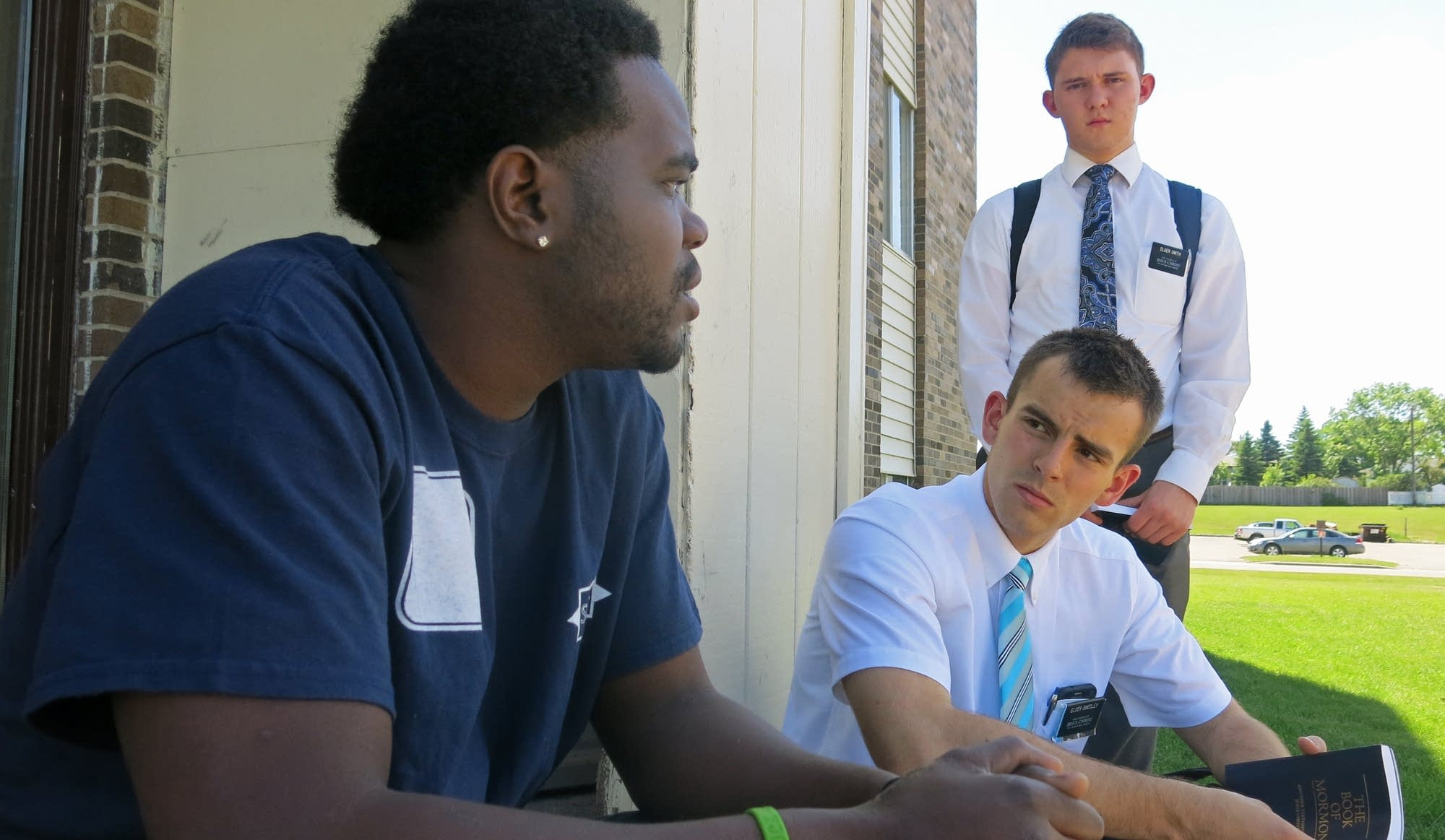 Young Mormon missionaries talk with a man identified only as Devontae.