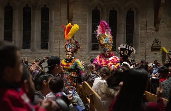 People wearing masks, colorful tunics and feathered hats dance in church