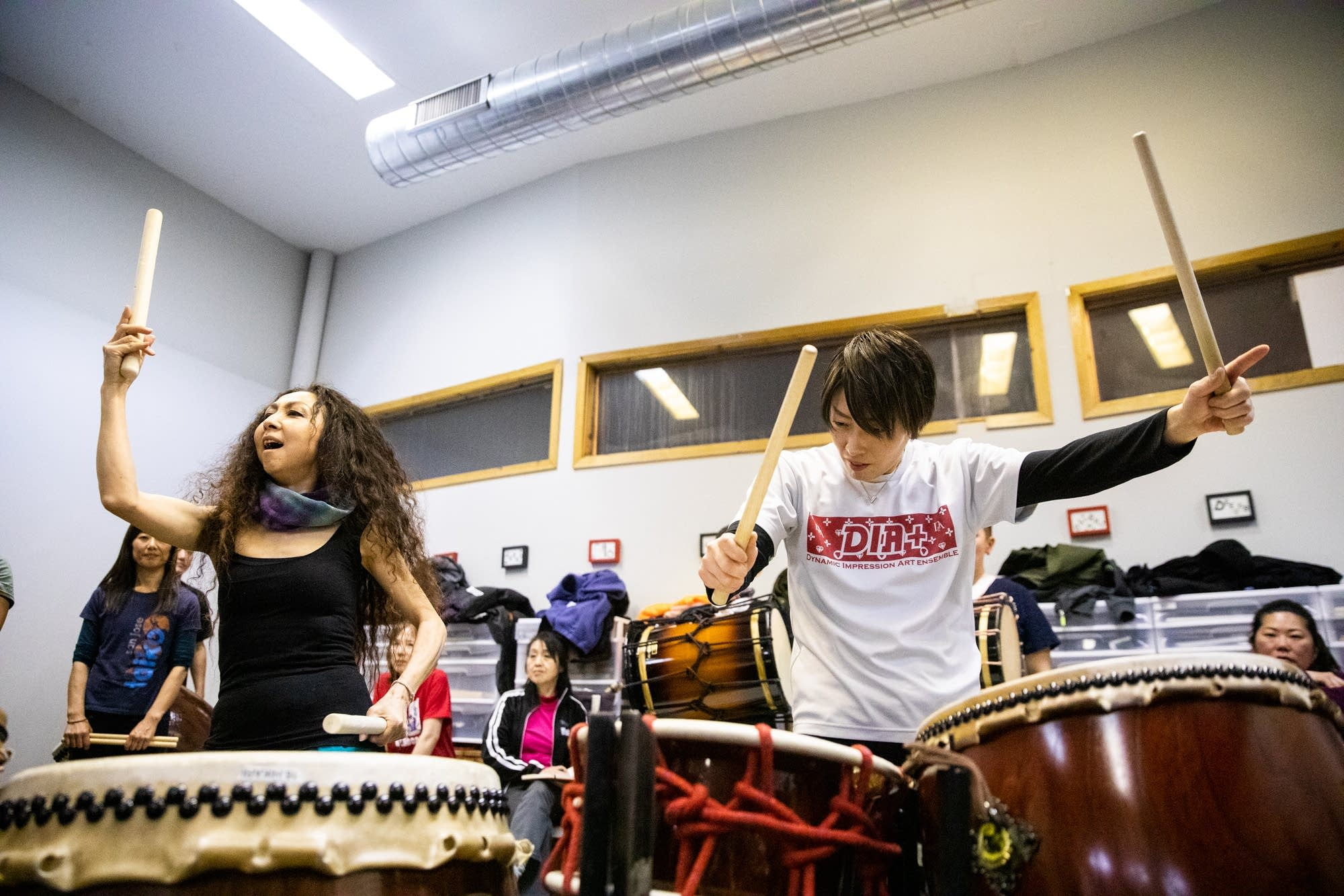 Two women passionately play large drums.