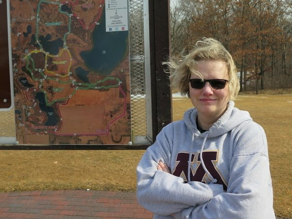 A woman stands outside near a hiking map display