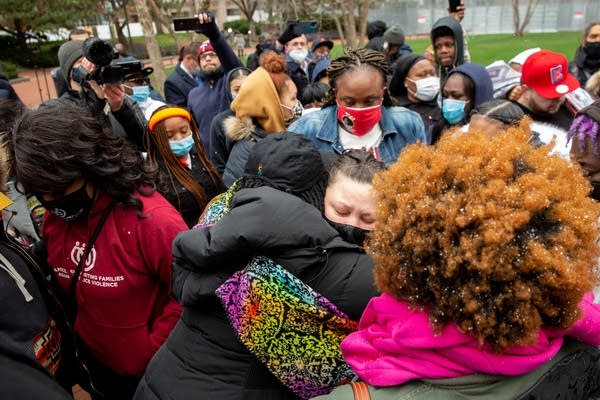 People hug in a large group.