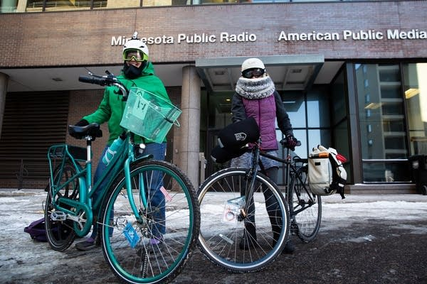 Two women stand in with their bikes and winter clothes.