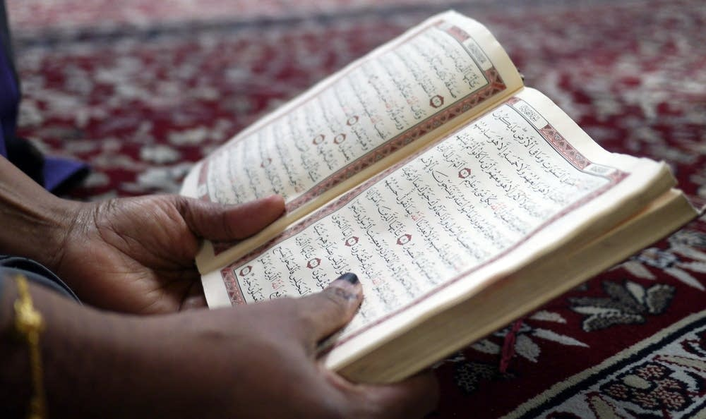 A woman reads the Quran during Friday prayers.