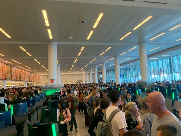 Travelers stand in long lines to clear customs at John F. Kennedy Airport