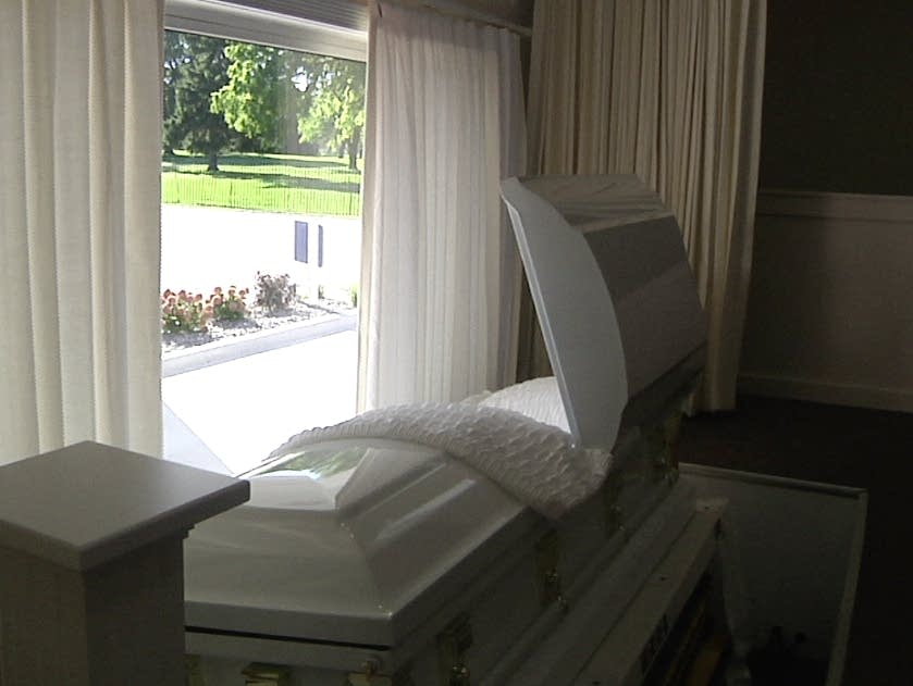 An empty casket sits in the window of a funeral home.