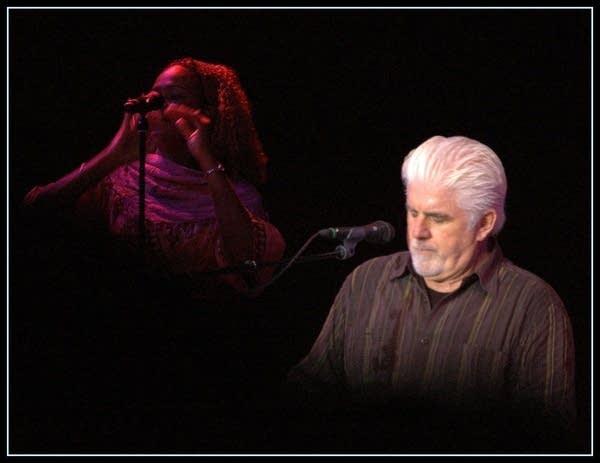 Singer Michael McDonald in concert, black bckgrnd, backup singer behind him