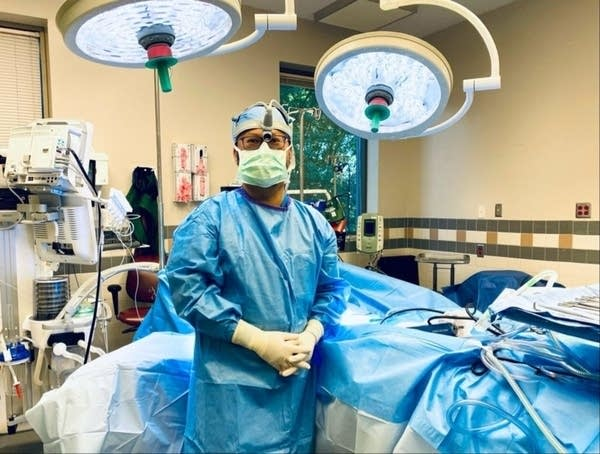 A man in surgical scrubs in an operating room.