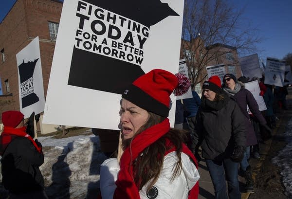 A person wearing a red hat and scarf holds a sign.