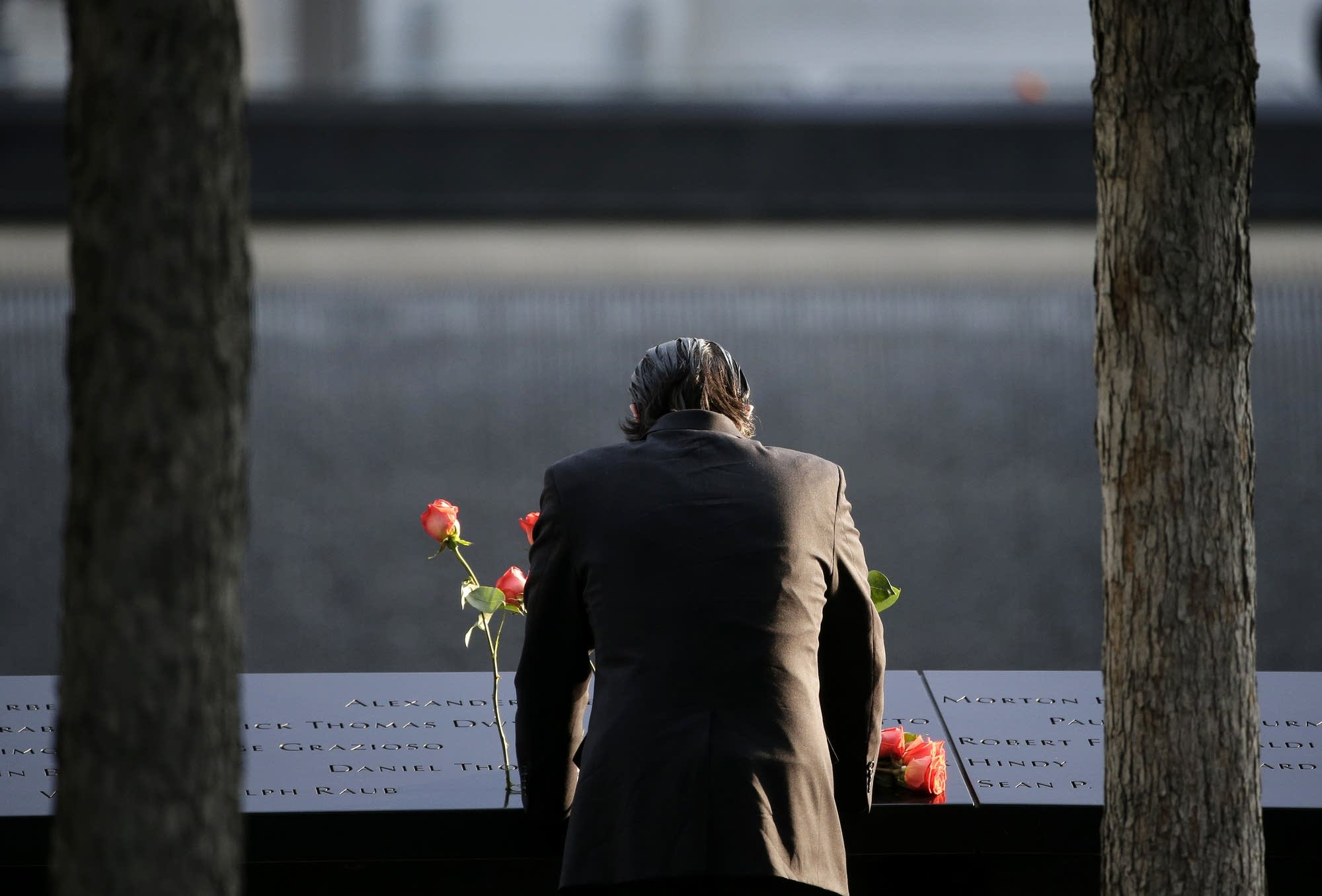 A man stands at the edge of a waterfall pool at ground zero.