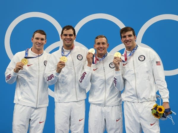 Four men hold up gold medals on a podium