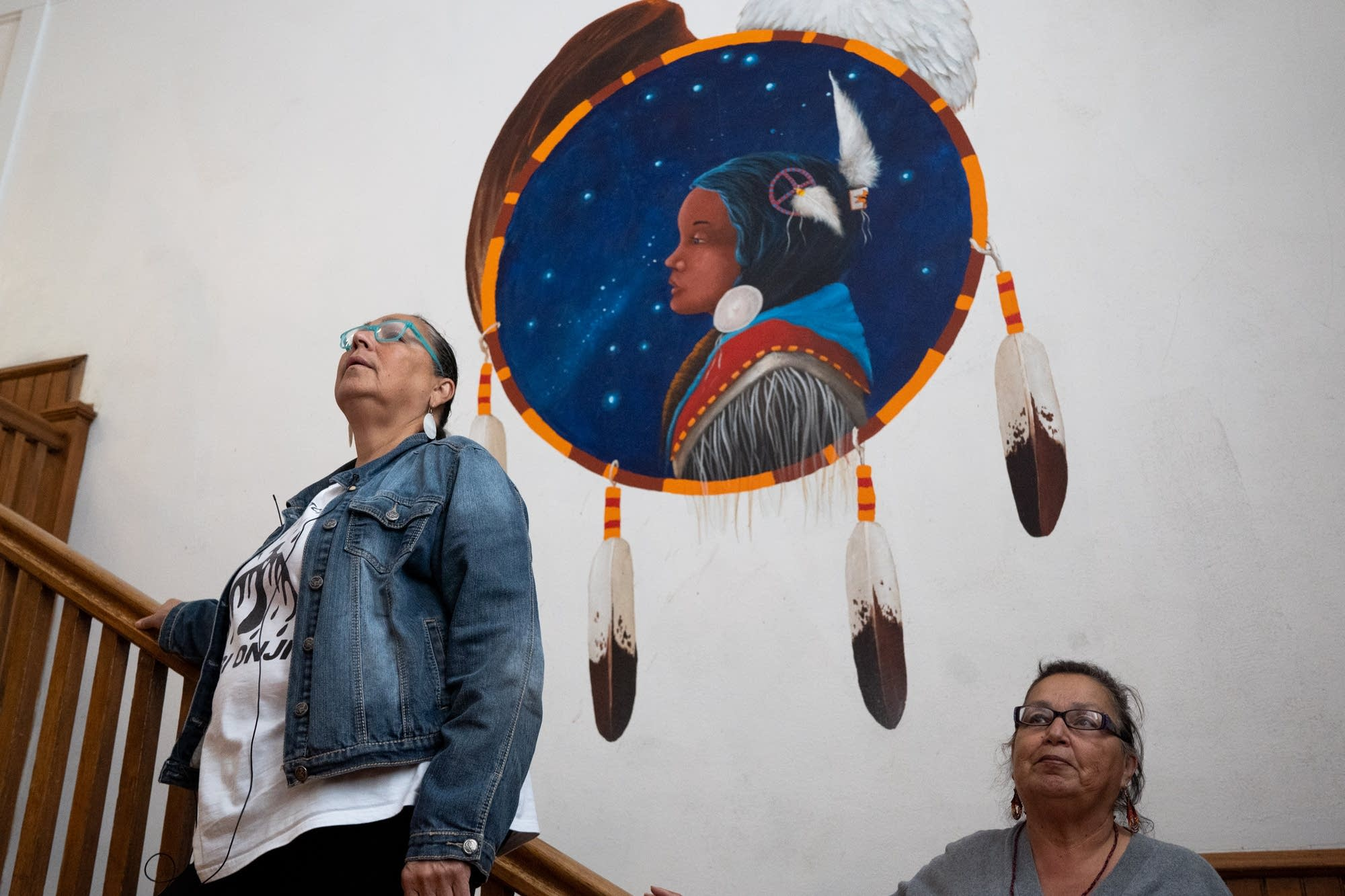 Two women stand on a staircase below a painting of a Native American.