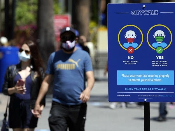 Signs instruct visitors on the proper way to wear masks; Signs instruct visitors on the proper way to wear masks at the Universal City Walk on Friday, May 14, 2021, in Universal City, Calif.