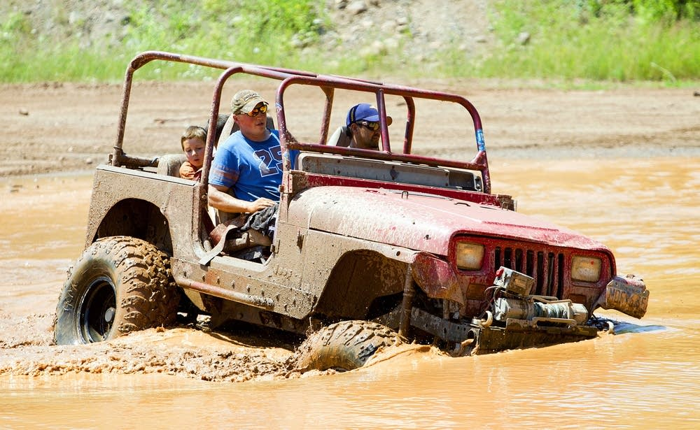 Jason Storrs driving through mud pit
