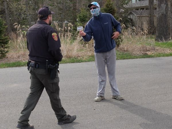 a conservation officer looks at a license held by a man wearing a mask