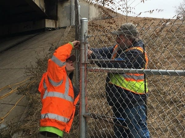 MnDOT workers install fencing around the homeless encampment site