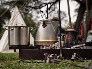 Cooking over a campfire using pots and kettles.