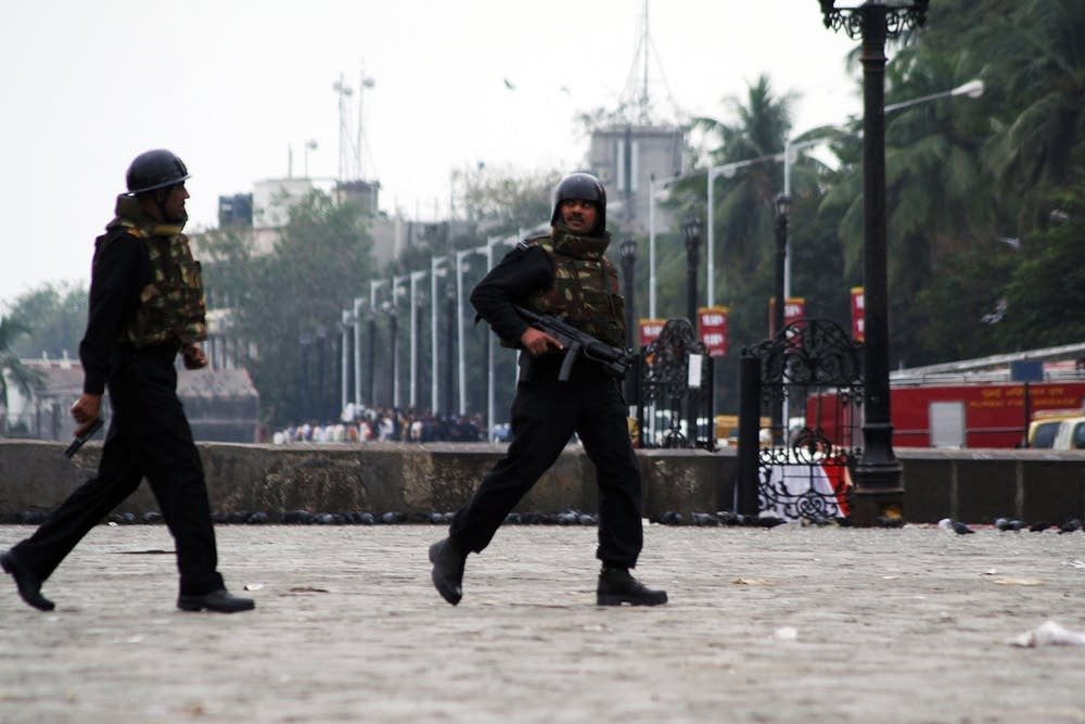Military personnel take up positions at the Taj Ma