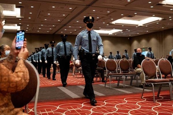 Police in uniform walk into a room.