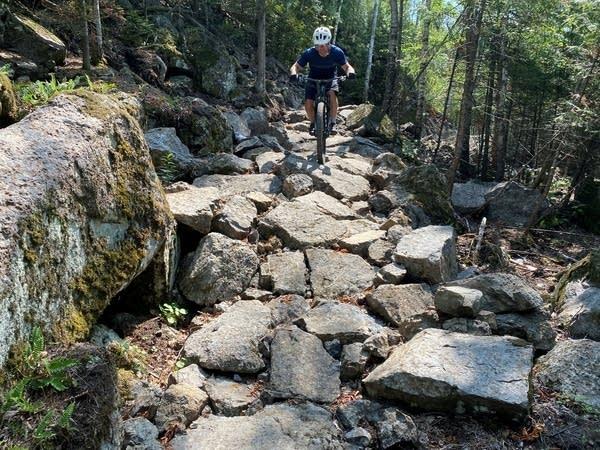 A person rides down a rocky mountain bike trail.