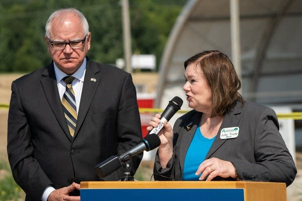 Julie Trude, right, speaks into a microphone next to Tim Walz outside.