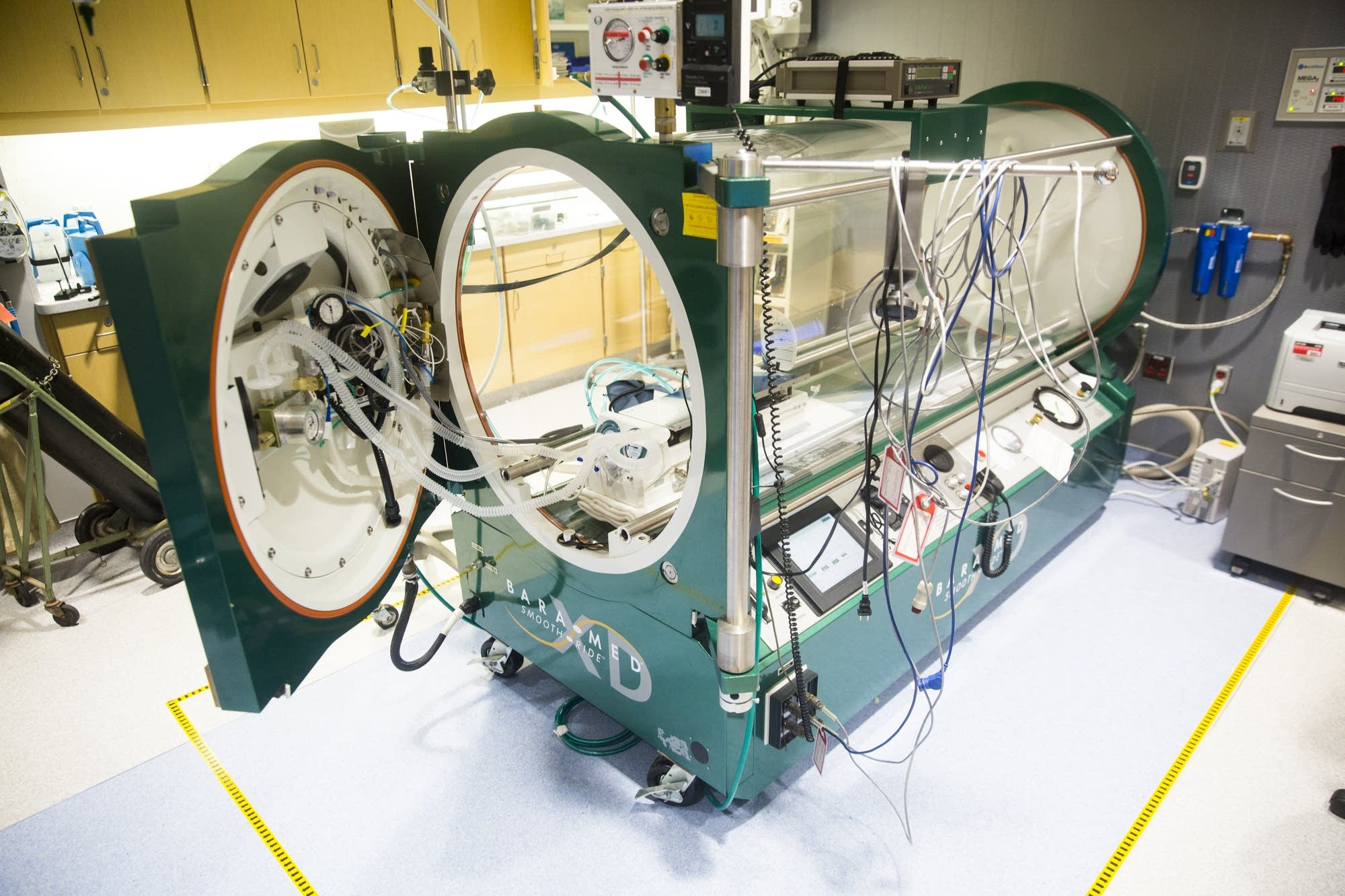 A monospace hyperbaric chamber sits empty.