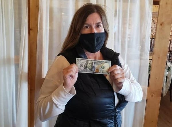 A woman in a mask holds a $100 bill.