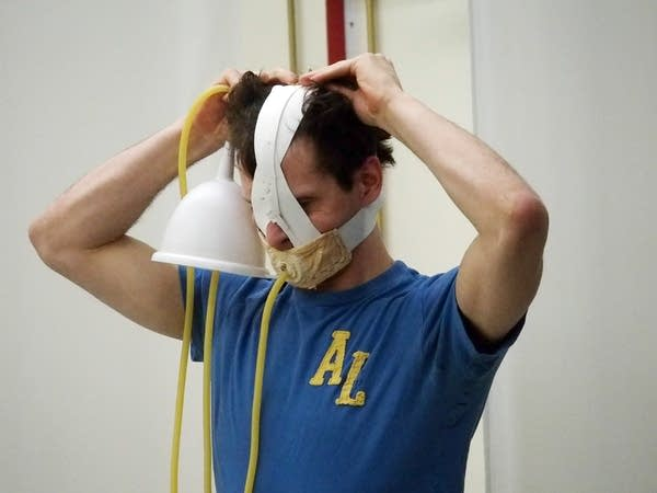 Dancer Andrew Lester tries on a mask used during the force-feeding scene.