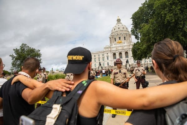 People stand with their arms around each other in front of police.