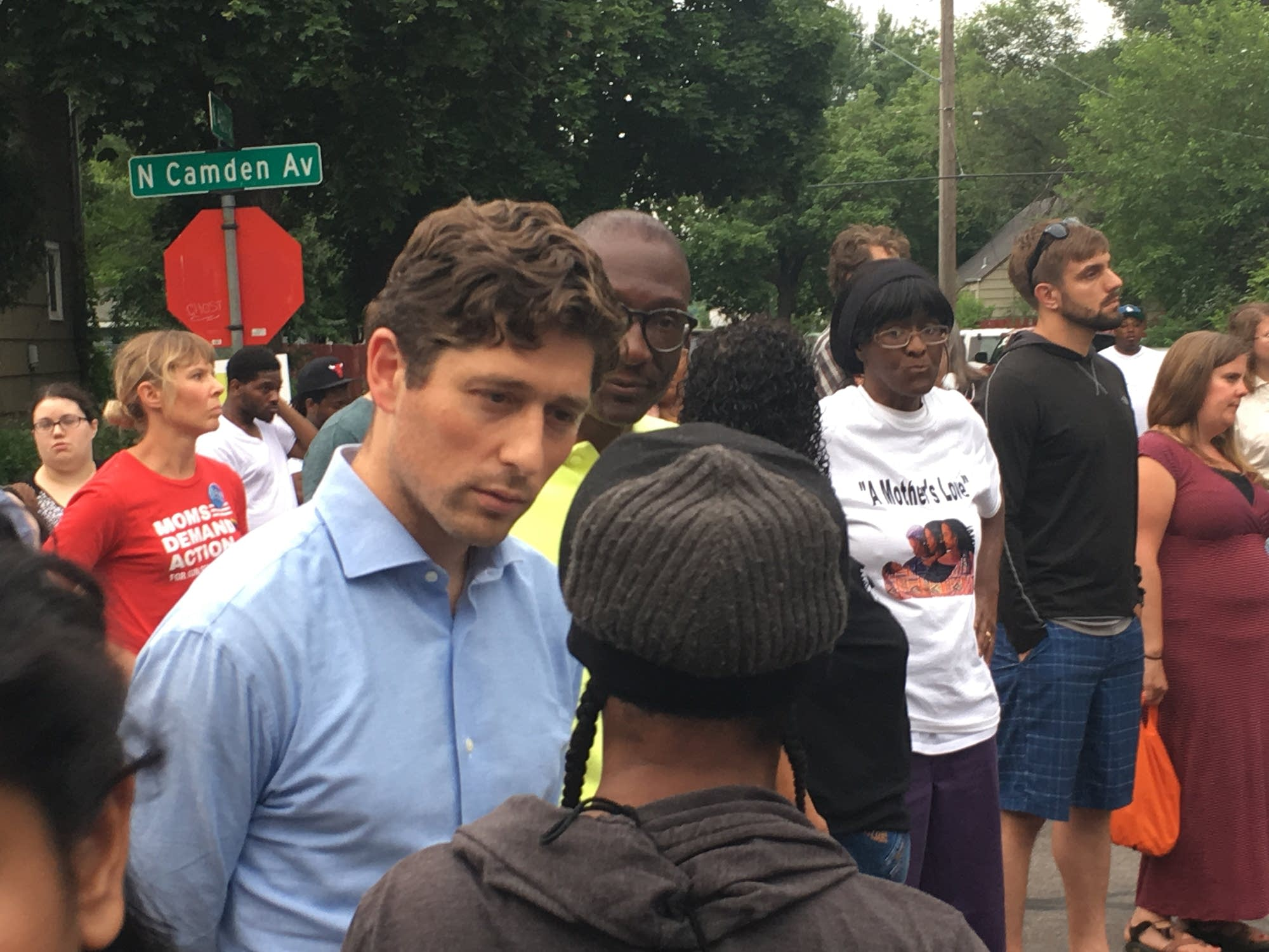 Mayor Jacob Frey talks with a woman attending a vigil.