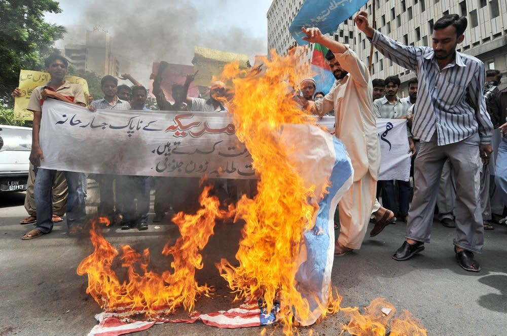 Activists of Islami Jam torch US and Israeli flags