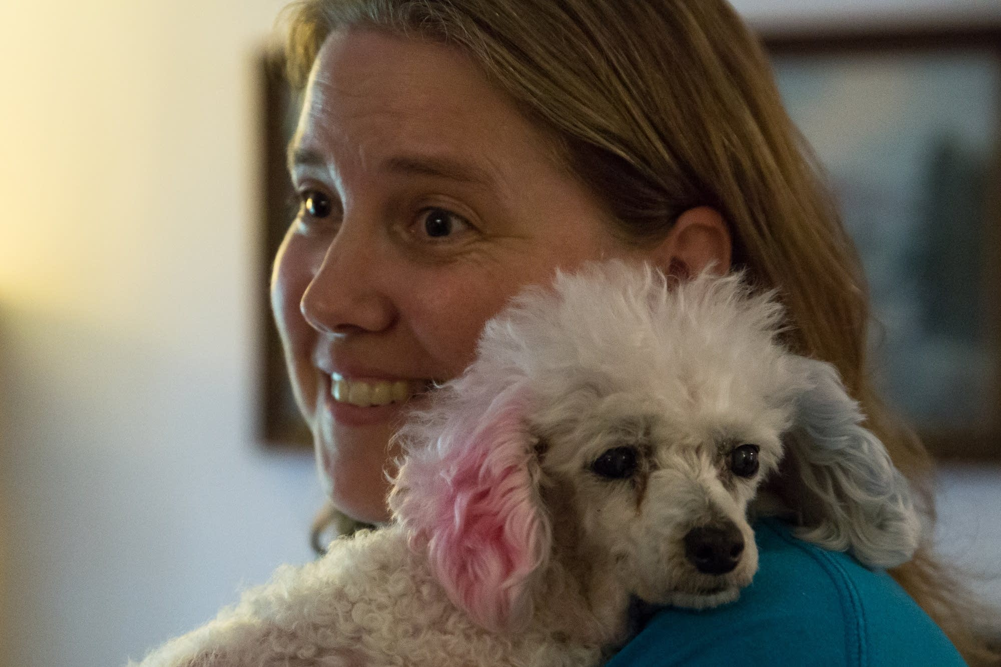 Eileen Hill, one of Peanut's owners, snuggles with her in the family room.