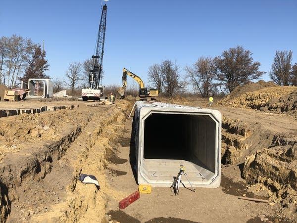 Crews work to install a large box culvert