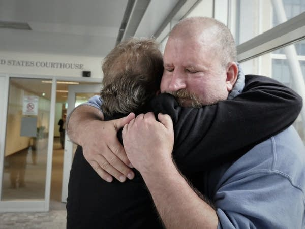 Clergy abuse victim David Lind, right, hugs fellow survivor