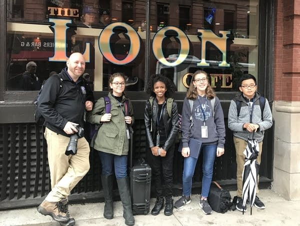 Teacher and students stand in front of a cafe.