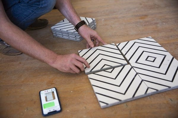 A contractor arranges tile in a pattern.